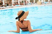 Young Woman Sitting Near The Pool. Sexy Girl With Healthy Tanned Skin. Female With Sun Hat Relaxing  poster