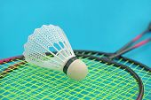 foto of game-cock  - Shuttlecock and badminton racket on blue background - JPG