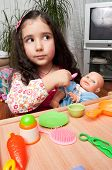 stock photo of child feeding  - little girl playing indoors feeding her doll - JPG