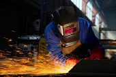 worker welding/grinding metal and sparks spreading