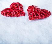 Picture of two beautiful romantic vintage red hearts tied together on a white snow background. Love and st. Valentines day concept.