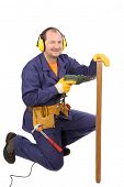 stock photo of muffs  - Worker in ear muffs with drill and board - JPG