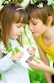 stock photo of nasal catarrh  - Little girl is blowing her nose brother gives her nasal spray - JPG