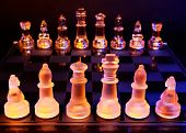 foto of chessboard  - Glass chess on a chessboard lit by a colorful blue and orange light and placed on a glass chessboard - JPG