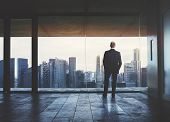 stock photo of thought  - Young business man standing on a balcony and looking at city - JPG