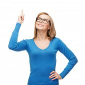advertisement concept - attractive young woman in casual clothes and black eyeglasses pointing her f