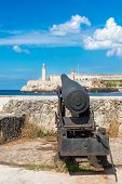 stock photo of el morro castle  - Old cannon aiming at the famous fortress of El Morro in Old Havana - JPG