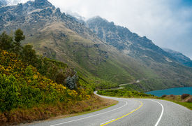 stock photo of long winding road  - A two lane road passes beside a lake and winds along the base of a misty mountain south of Queenstown on New Zealand - JPG