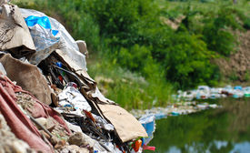 foto of non-biodegradable  - Discarded industrial waste being dumped nead water - JPG