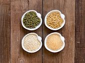 stock photo of quinoa  - Raw Organic Amaranth and quinoa grains wheat and mung beans in small bowls - JPG