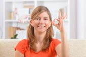 stock photo of deaf  - Beautiful smiling deaf woman using sign language or showing OK sign - JPG