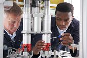 stock photo of supervision  - Engineer And Apprentice Working On Machine In Factory - JPG