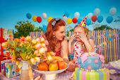 picture of fussy  - Young mother comforts crying baby girl in birthday hat - JPG