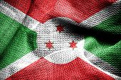 image of burundi  - Texture of sackcloth with the image of Burundi flag - JPG