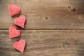 picture of valentine candy  - Heart shaped Valentines Day candy side border on a wooden background - JPG
