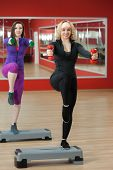 picture of step aerobics  - Two smiling sporty pretty girls practice step aerobics with dumbbells in sports hall - JPG