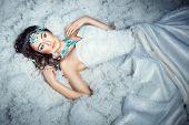 image of faerie  - Girl in white dress lying on white fur - JPG