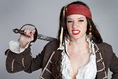 stock photo of wench  - Angry pirate woman holding sword wearing costume - JPG