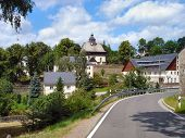 stock photo of municipal  - View on the old fortified church and houses of a municipality in the Ore Mountains in Saxony - JPG