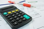 pic of statements  - calculator and a red ballpoint pen on bank statements - JPG