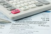 picture of statements  - calculator and silver ballpoint pen sitting on a bank statement with focus around the payment due date - JPG