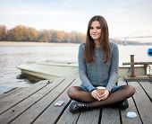 foto of jeans skirt  - Young beautful brunette woman in blouse and denim skirt sitting on the river pier with coffee and her smartphone - JPG