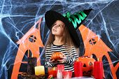 picture of warlock  - Little girl Witch in hat on Halloween decorations background - JPG