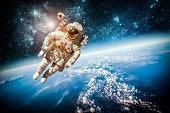 stock photo of gravity  - Astronaut in outer space against the backdrop of the planet earth - JPG