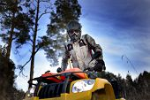 stock photo of four-wheel drive  - Horizontal close-up of a man in helmet and safety goggles looking into the camera while sitting on quad bike against vivid blue sky.