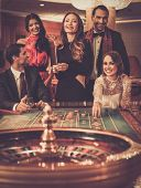 stock photo of gambler  - Group of stylish people playing in a casino - JPG