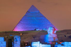 picture of triangular pyramids  - CAIRO EGYPT - JANUARY 1 2009: Giza pyramid and Sphinx light up for magical sound and light show. ** Note: Visible grain at 100%, best at smaller sizes - JPG