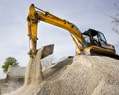 pic of heavy equipment operator  - Excavator loading truck with gravel and dirt on the road construction site - JPG