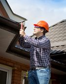image of handyman  - Portrait of young handyman repairing house roof with nails and hammer - JPG