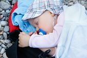pic of pacifier  - Sleeping baby with a pacifier lying on a pebbled beach in improvised bed during a family vacation - JPG