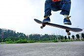 foto of skateboarding  - young skateboarder  legs doing skateboarding trick ollie outdoor - JPG