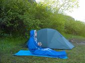 foto of sleeping bag  - The man is resting in a sleeping bag on the background of tents and green forests - JPG