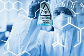 pic of hazardous  - Science graphic against scientist in protective suit with hazardous chemical in flask - JPG