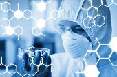 image of scientist  - Science graphic against scientist in protective suit analyzing pills - JPG