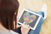 picture of aspergers  - Girl using a tablet pc sitting on the floor against autism awareness heart - JPG