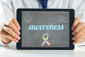 pic of autism  - The word awereness and autism awareness ribbon against medical biology interface in blue - JPG