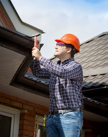 stock photo of handyman  - Portrait of young handyman repairing house roof with nails and hammer - JPG