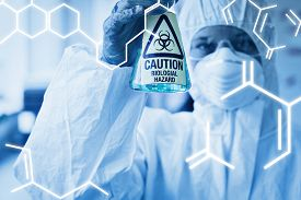 stock photo of hazardous  - Science graphic against scientist in protective suit with hazardous chemical in flask - JPG