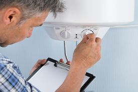picture of temperature  - Plumber Holding Clipboard Adjusting Temperature Of Electric Boiler - JPG
