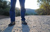 stock photo of dirt road  - A man standing on a gravel road with his shadow in front of him - JPG