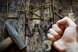 stock photo of labor  - man holding a wrench in his hand on the background the inscription labor day selective focus - JPG
