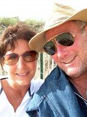 stock photo of middle-age  - happy handsome middle age guy with sunglasses smiling with woman - JPG
