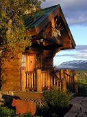 pic of log cabin  - Entryway to a log house with mountains in the background - JPG