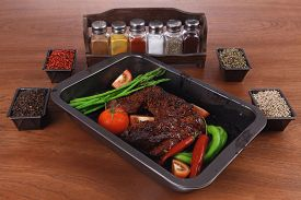picture of peppercorns  - fresh glazed baked big beef meat rib chunk under sweet sauce with tomatoes hot chili pepper asparagus different peppercorn spices in black deep tray on light walnut wooden table - JPG