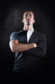 foto of half-dressed  - Confident rugby player with arms crossed against half a suit - JPG