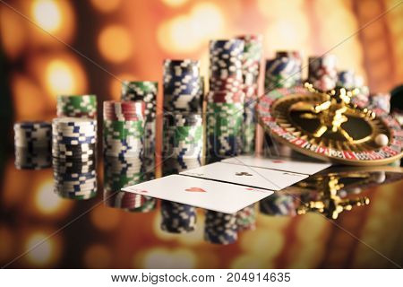 Casino theme. High contrast image of casino roulette, poker game, dice game, poker chips on a gaming table, all on colorful bokeh background.
